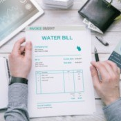 Man holds invoice of water usage over desk.