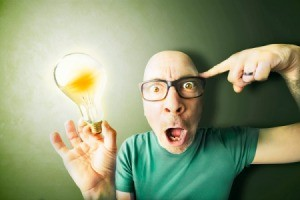 Man making funny face holding lit light bulb