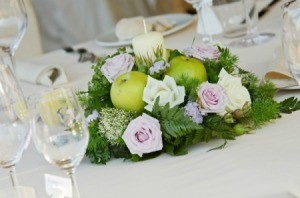 Candle centerpiece with apples roses and sprigs of fir.