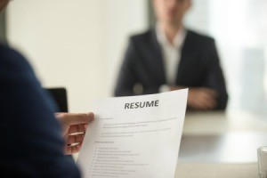 Man sitting down to interview looking at resume