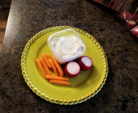 A plate of ranch dip with vegetables.