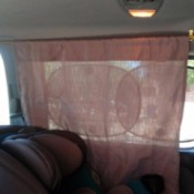 A curtain in a minivan next to a carseat.