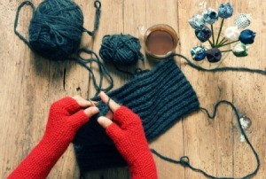 Person wearing red fingerless gloves knitting something grey.