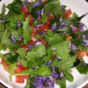 A green salad with fresh ingredients and purple flowers.