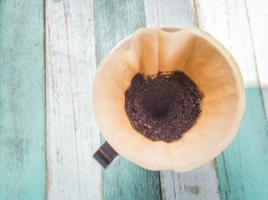 Coffee filter with coffee grounds on a painted wood backdrop.