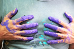 Hands with paint touching a gray shirt.