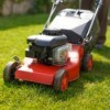 Red lawn mower on fresh cut grass.