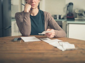 Woman sitting in kitchen working on her budgeting