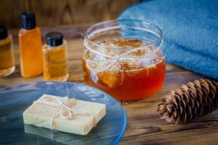 Honey Hair Treatment with towels and soap on a wood table