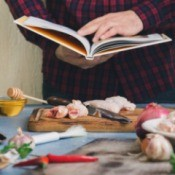 Man reading recipe book while prepping chicken surrounded by ingredients
