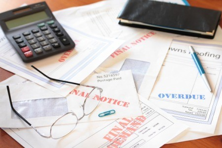 Too many overdue bills piled up on desk.