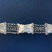 An old silver bracelet with a floral pattern.