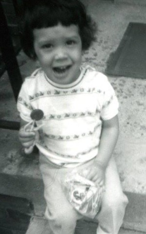 A black and white photo of a child holding a lollipop.