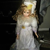 Value of a Porcelain Doll - doll wearing a white satin dress and hat