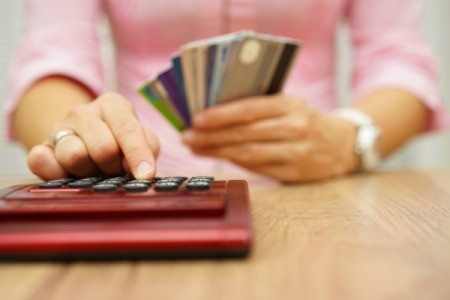 Woman holding a stack of credit cards and typing into a calculator.