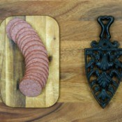 Sliced summer sausage on a cutting board.