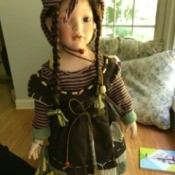 Identifying a Porcelain Doll - doll wearing a brown dress with striped shirt underneath