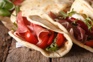 Italian piadina flatbread stuffed with ham and vegetables close-up