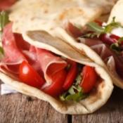 Italian piadina flatbread stuffed with ham and vegetables close-up