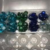 Glass gems organized inside a clear plastic egg carton.