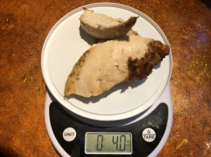 A plastic lid on top of a food scale, weighing chicken breasts.