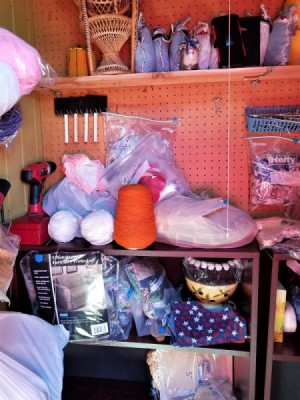 A disorganized shelf top containing craft supplies.