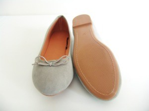 Grey slip on women's shoes, one upside down.