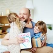 Girls giving happy dad father's day gift and card