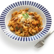 Goulash in a bowl, topped with cheese.