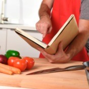 Unrecognizable man at kitchen following recipe book.