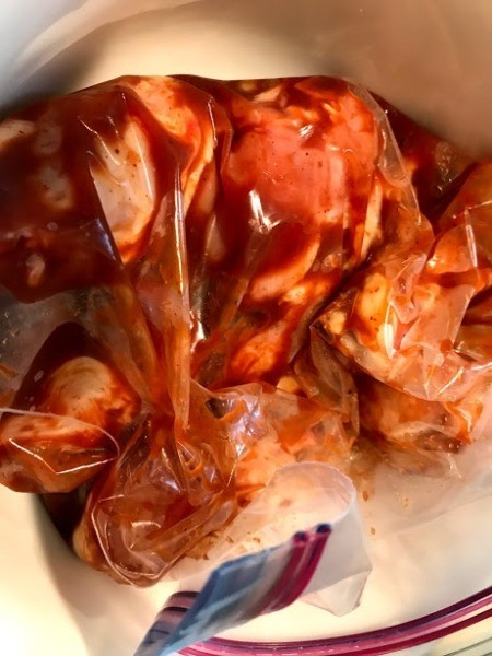 Chicken in a plastic bag with BBQ sauce being marinated.