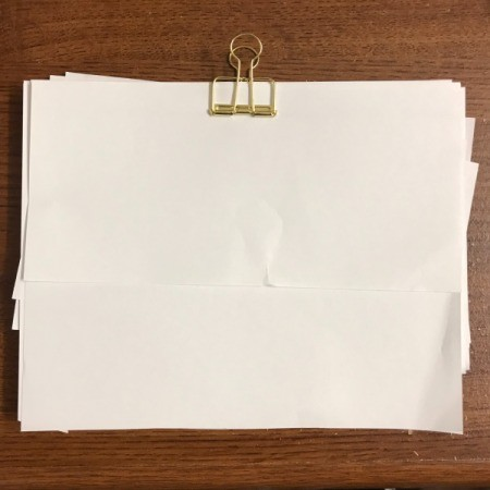 A clip holding scrap paper to be used for notes.