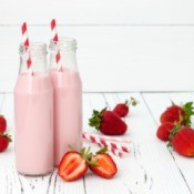 Strawberry milk in glass bottles with paper straws.