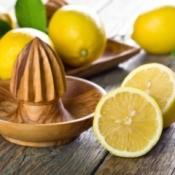Wooden lemon juicer surrounded by lemons.