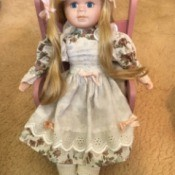 Identifying a Porcelain Doll  - doll with long blond hair sitting on a pink chair