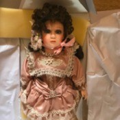 Value of Franklin Heirloom Porcelain Dolls - dark haired doll wearing a dusty rose dress