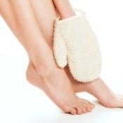 Women using exfoliating glove on legs.