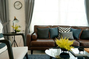 Brown leather sofa with throw pillows.