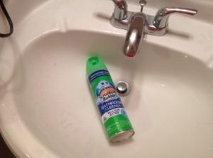 A bottle of scrubbing bubbles inside a bathroom sink.