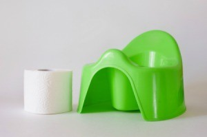 Green plastic potty chair, with a roll of toilet paper.