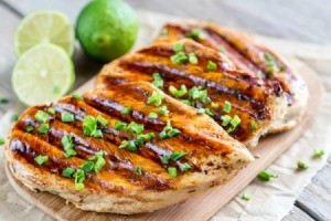 Grilled Chicken on a cutting board with limes.