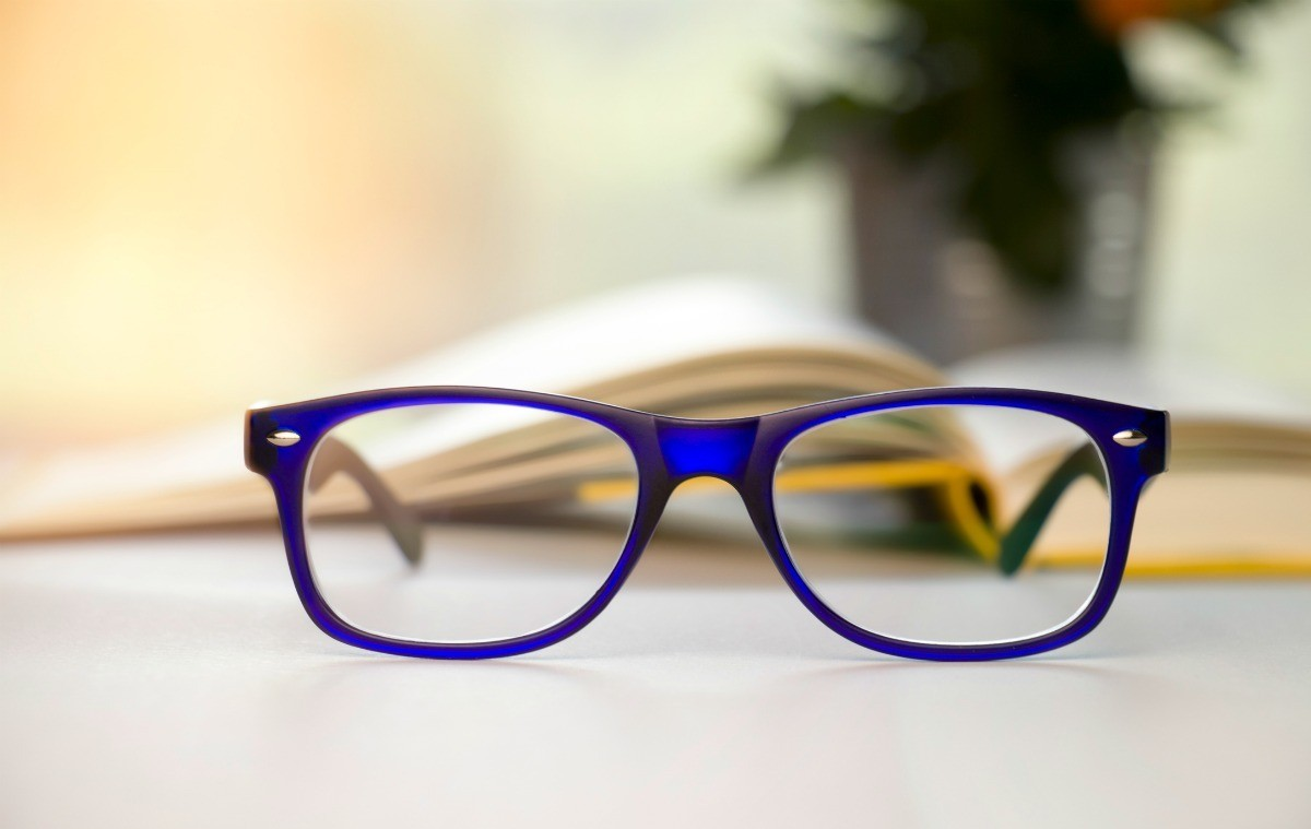 2496b4734ab7 Stylish blue glasses on a blur background. This is a guide about buying  inexpensive reading ...