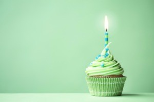 Green cupcake with a blue and green candle.