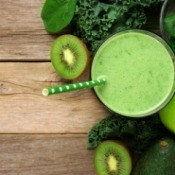 Top view of a green smoothie surrounded by green fruits and veggies.
