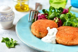 Salmon Patties on a blue plate with greens.