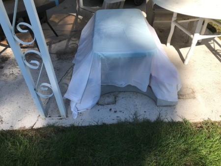 An outdoor table covered with a plastic shower curtain liner.