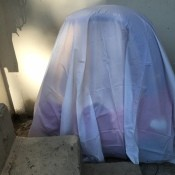 An outdoor car covered with a plastic shower curtain liner.