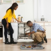 Man and woman fixing a dishwasher.
