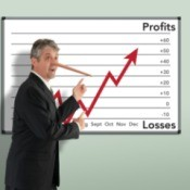 Businessman with Pinocchio nose pointing at a profit loss chart that is going up.