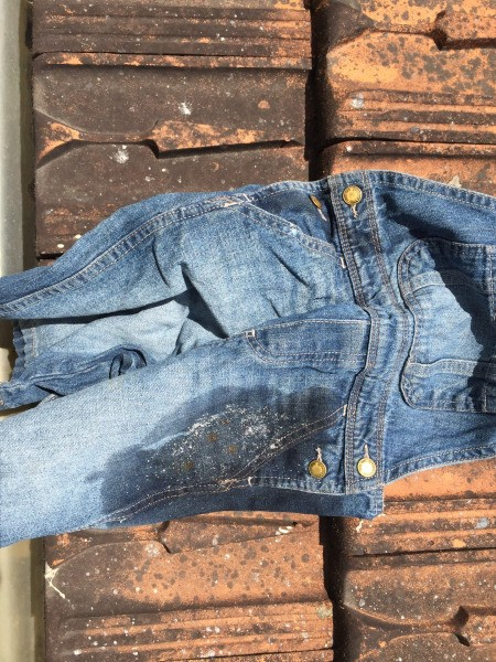 Vinegar treating a rust stain on overalls.
